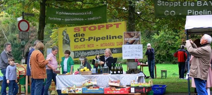 Gesundes gegen Giftiges: Proteststand mit Obst und Säften. Plakate: «Stoppt die CO-Pipeline!», «Kohlenmonoxid: farblos, geruchlos, tödlich.».