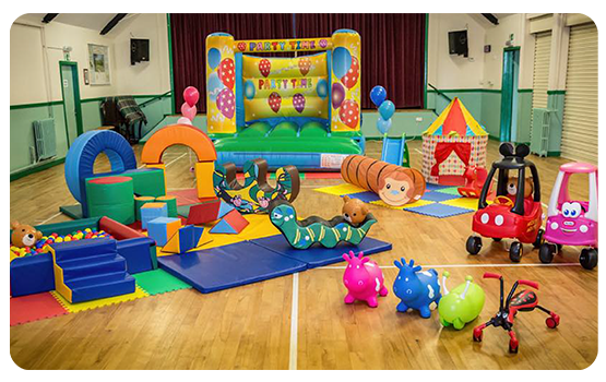 a play area in a hall with soft toys and a jumping castle