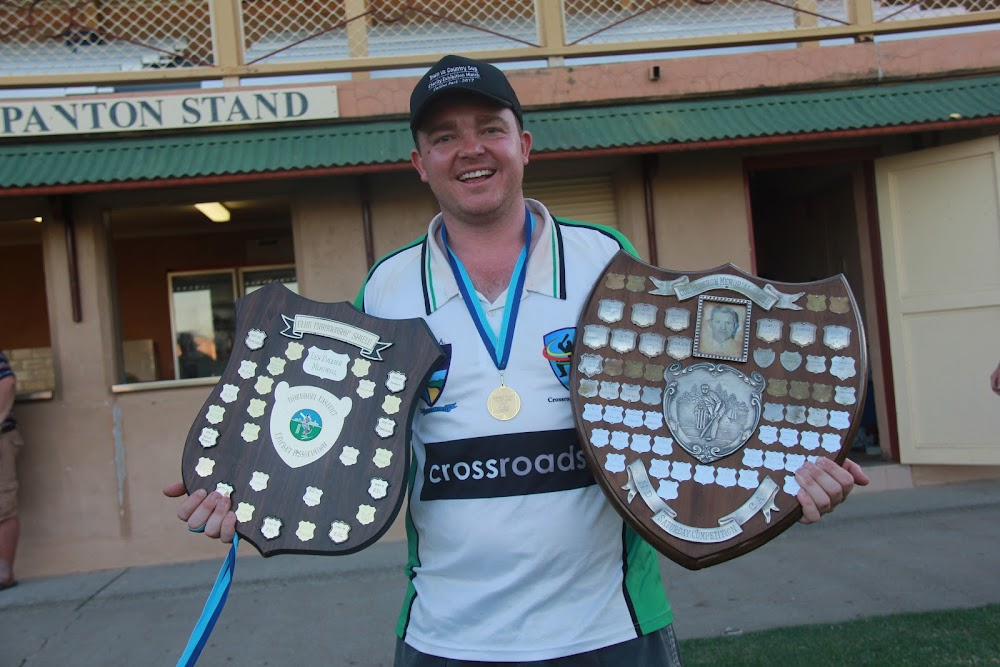 Crossroads Hotel first grade captain and president Luke Meppem with the club championship and first grade premiership shields after his side's 37-run win on Saturday.