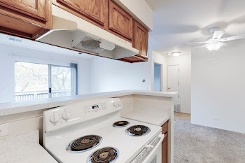 Fully-equipped kitchen with wood cabinets and white appliances looking into the living room