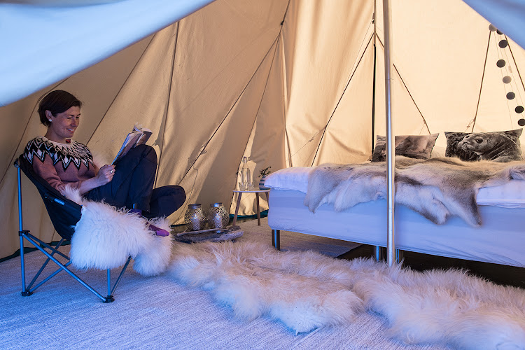 Greenlandic host Anika Krogh reads inside her tent at Camp Kiattua.
