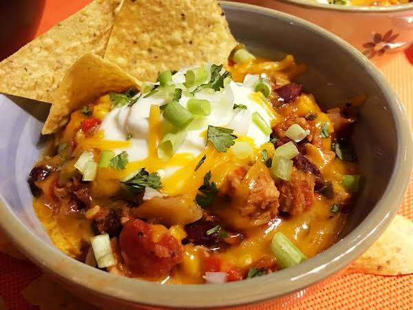 Turkey Chili In A Bowl Garnish With Sour Cream, Green Onions And Tortilla Chips.