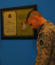 Photo: Specialist Brandon Hempel, driver and gunner with the 34th Military Police Company, 34th Infantry Division, a native of Spring Grove, Minn., bows his head in a moment of silence for his fallen comrade, Spc. Daniel Drevnick, of Woodbury, Minn., during a dedication ceremony in the combined gym and USO at Contingency Operating Base Basra, Dec. 31.
