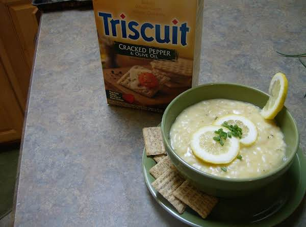 Our Favorite Lemon Orzo Soup Garnished With Fresh Lemon Slices And Our Favorite Crackers