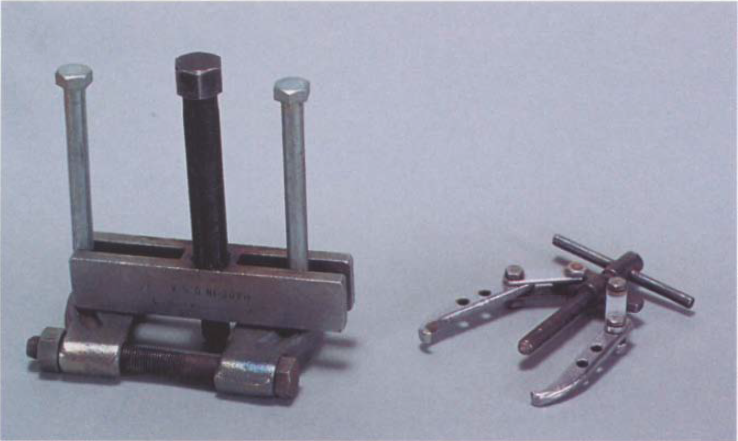 Bearing pullers are used to remove the bearings from a headstock spindle. The puller at right is for removing small bearings from shaft assemblies, while the larger model at left can adjust to a variety of situations.