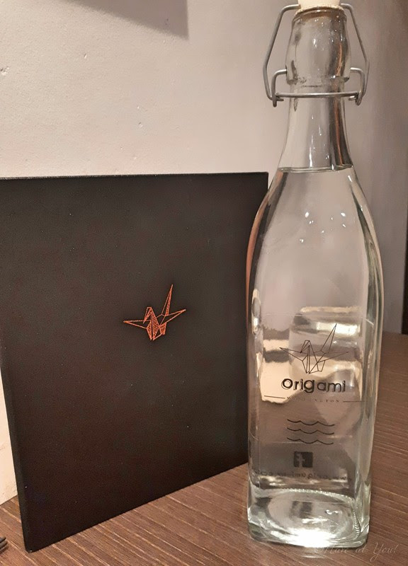 Origami's water bottle and menu cover with the image of a paper crane