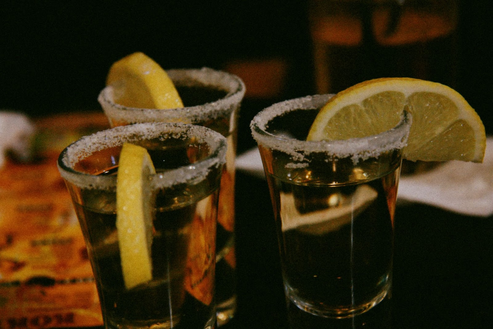 Three shot glasses filled with coconut tequila, and lemon wedges.