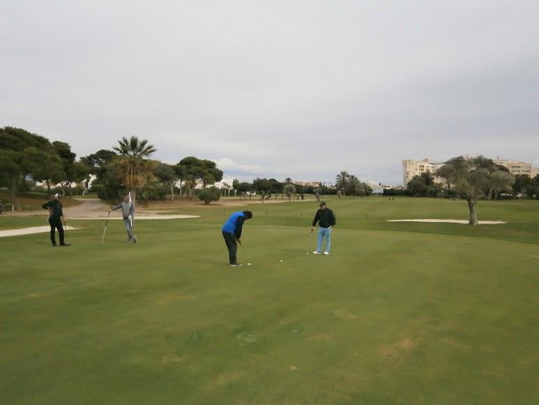 Golfistas embocando uno de los hoyos del recorrido.