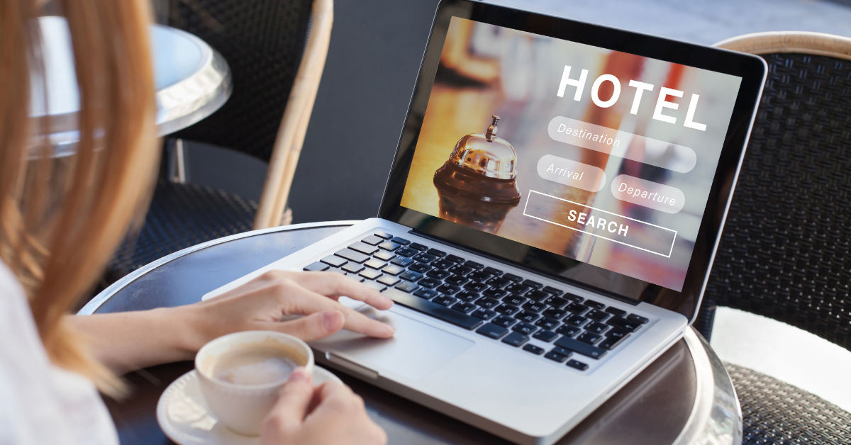A woman booking a hotel reservation on the computer while having a cup of coffee.