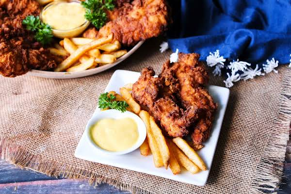 Fried Chicken Strips On A Plate With French Fries.