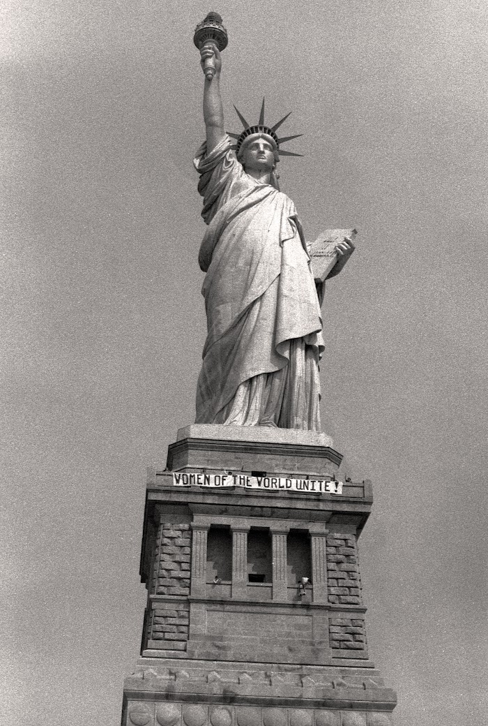 The Statue Of Liberty with a banner that reads Women of the world unite