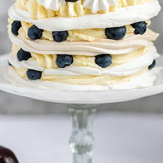 Meringue Stack Cake with Whipped Cream, Lemon Curd, and Berries.