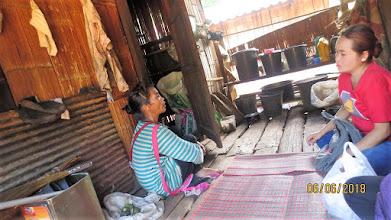 Photo: Pon (Lahu volunteer Healthcare worker) talks to patient in Lahu language