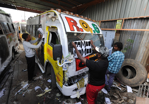Artists put graffittis and stickers on a privately-owned public transport bus, popularly known as 'matatu' at a workshop in a suburb of Nairobi on April 14, 2016. For those who can afford a ticket the matatu -- traditionally a minibus taxi with simple coloured stripes along the sides -- is the transport option of choice: around 90 percent of Nairobi's commuters board one daily. Competition for customers is fierce and a pimped ride can make all the difference.