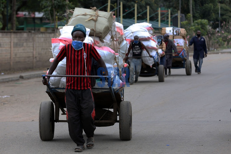 Cart pusher ferries food into Eastleigh in Nairobi on May 21, 2020.