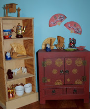 Photo: Some of my odds and ends.    The wooden carvings (top and middle shelf on the book case and on the cabinet) were brought back from Asia many years ago by a family friend who was a merchant marine.  They are hand carved and quite fabulous.  My dad made the book case and I found the cabinet at a department store.  The fans hanging on the wall are printed on paper and cut out.