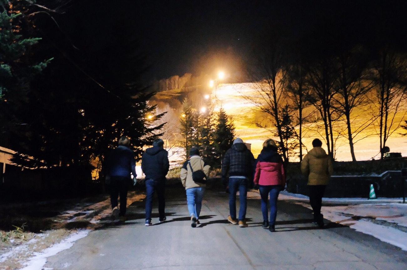 夜に歩道に歩いている人たち  中程度の精度で自動的に生成された説明