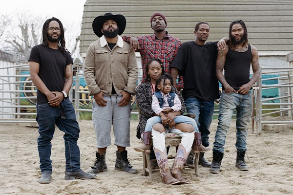 The Compton Cowboys posing for a photo in their backyard ranch with Keiara's daughter Taylor on her lap.