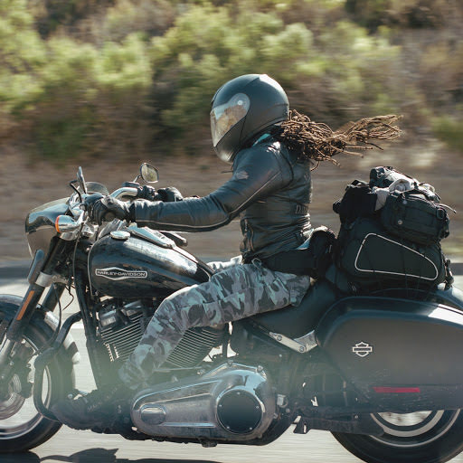 A woman riding her motorcycle with her hair flying in the wind.