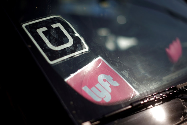 A driver displays Uber and Lyft ride sharing signs in his car windscreen. Picture: REUTERS