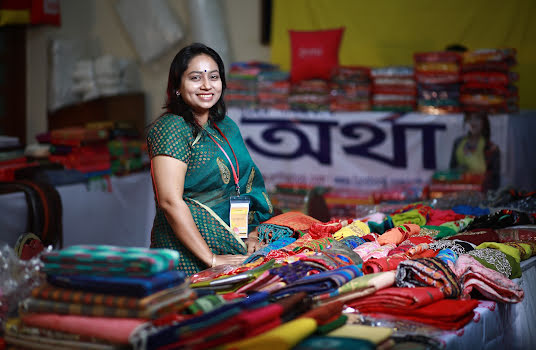 Smiling woman selling brightly coloured textiles at a market.