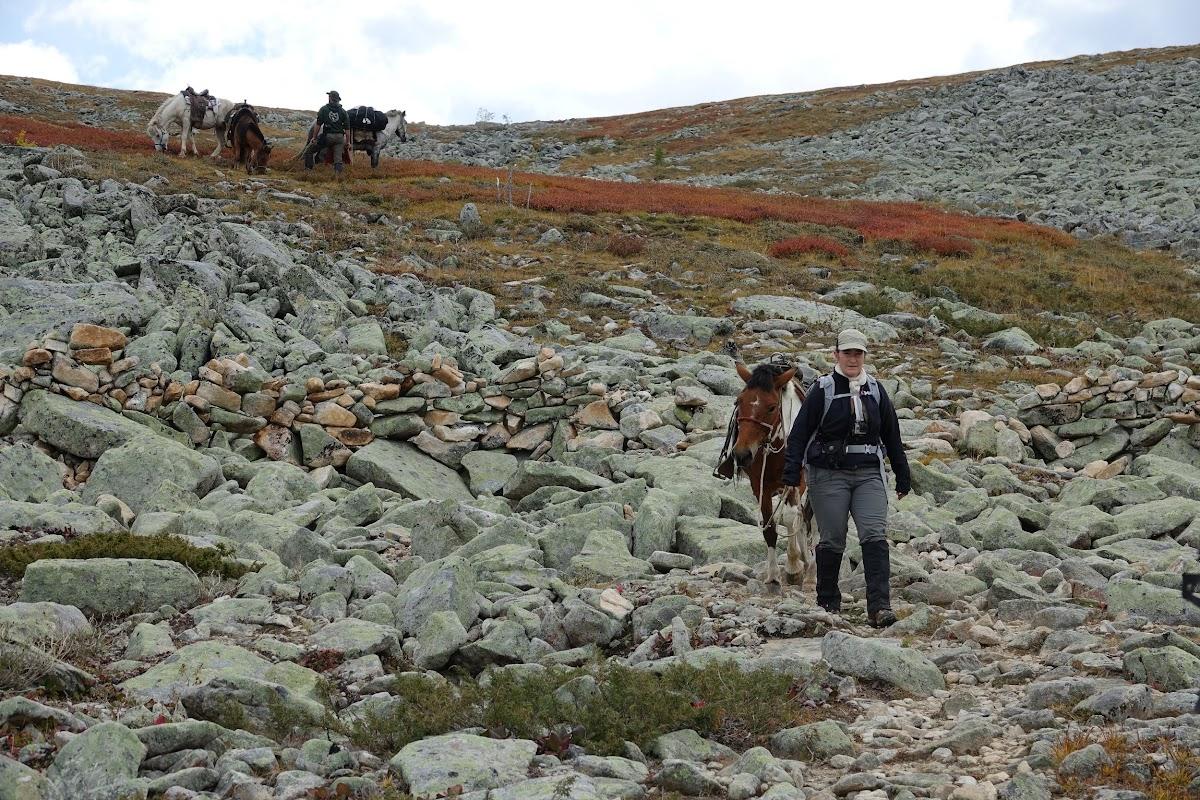 Patricia menant son cheval sur la pente raide et rocheuse