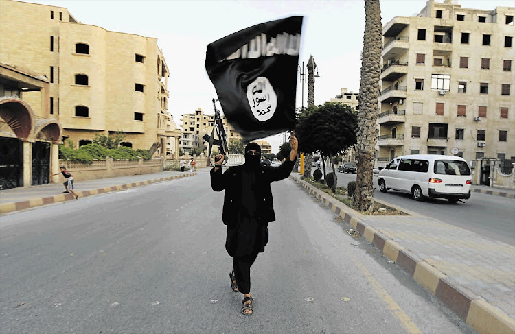A militant of the Islamic State waves the group's flag. File photo.