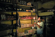 An owner of a convenience store, or spaza shop, picks an item for a customer as he holds a candle during Eskom's load-shedding.