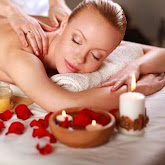 a massage being given to a lady with candles and petals next to her