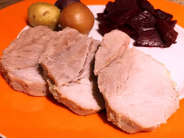 Three Slices Of Pork With Baby Potatoes And Beets On An Orange/white Plate.