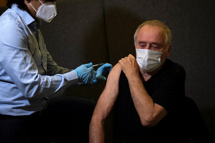 Joesph Carroll receives the first of two injections of the Pfizer-BioNTech Covid-19 vaccine at the Hurley Clinic in London, Britain. Picture: Aaron Chown/PA Wire/Pool via REUTERS