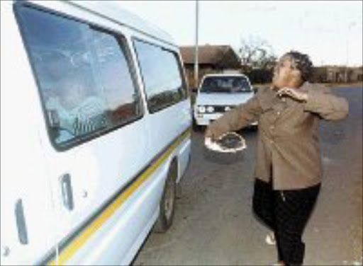 CRYING SHAME: Tearful Maki Bam, a caregiver at Siyakhula Orphanage, chases after a minibus containing hysterical children removed from the orphanage after the government decided to close it down. Behind the minibus is a police escort vehicle. Pic. Len Kumalo. © Sowetan.