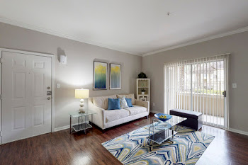 Model living room with wood-inspired flooring, light gray walls, patterned area rug, and light couch