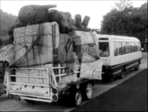 SKY HIGH: An overloaded trailer, hitched to a bus, travels on the N4 highway towards Mozambique. Pic. Riot Hlatshwayo. 06/07/08. © Sowetan.
