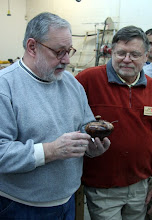 Photo: Michael Blake showing the covered salt bowl turned from the last of his pignut hickory burl by Richard Webster. Michael made the spoon.