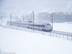Photo: Flytoget (Oslo Airport Express) BM71 train running through snowy weather outside Drammen
