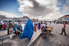 vrouw in blauwe boerka loopt langs, naast een weg zittende, verkopers