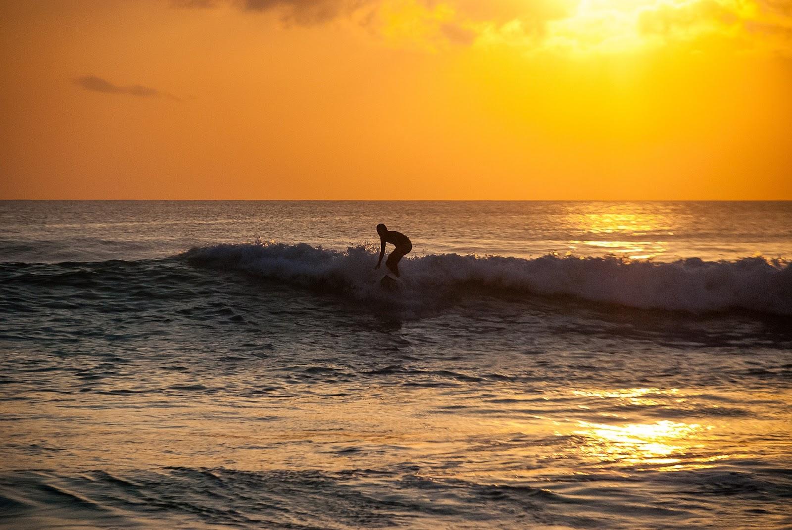surfer surfing blue ocean wave during sunset in medewi bali indonesia