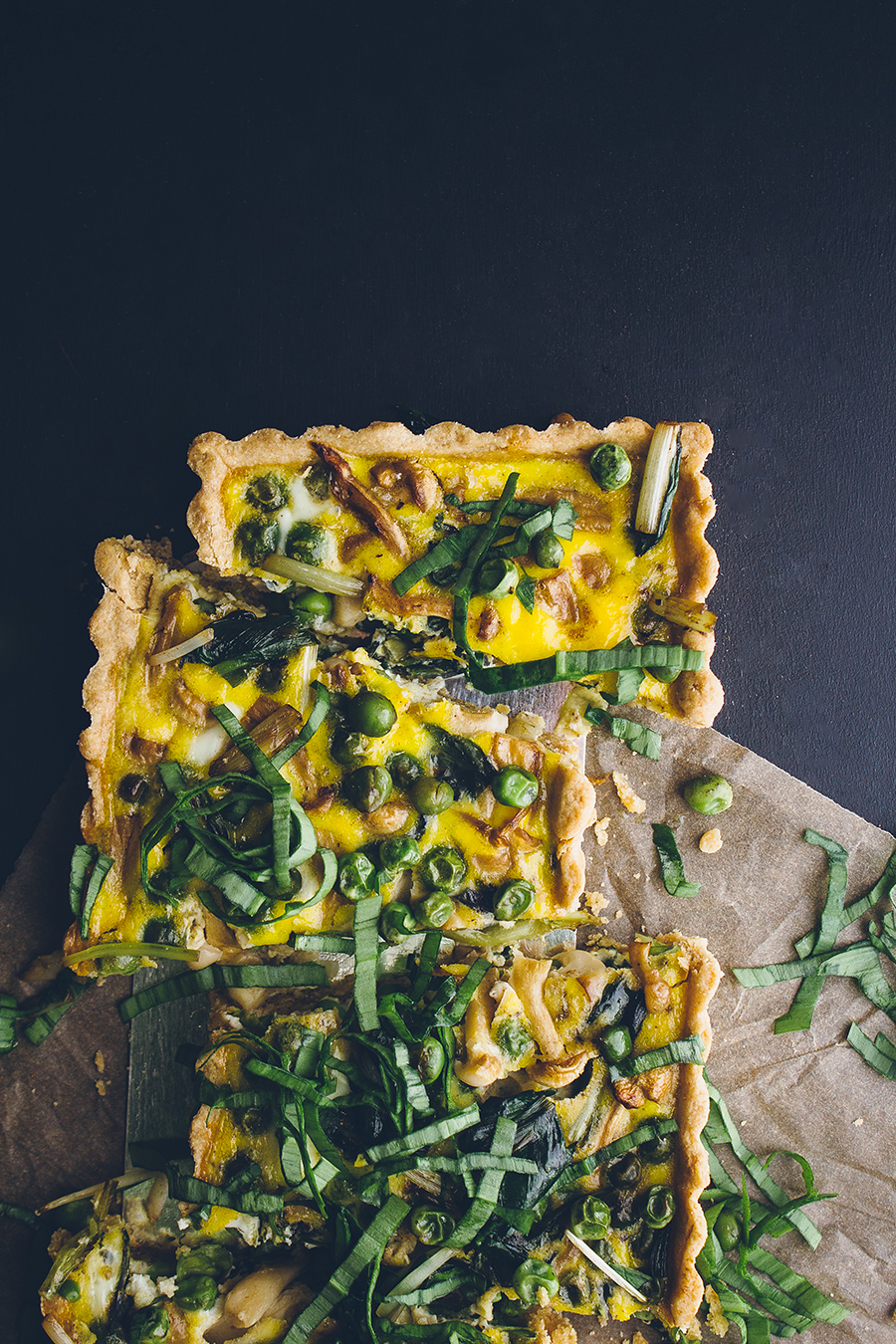 Quiche with vegetables garnished with ramp slices.