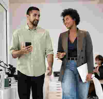 A man and woman walk down an office hallway, chatting and carrying their mobile devices.
