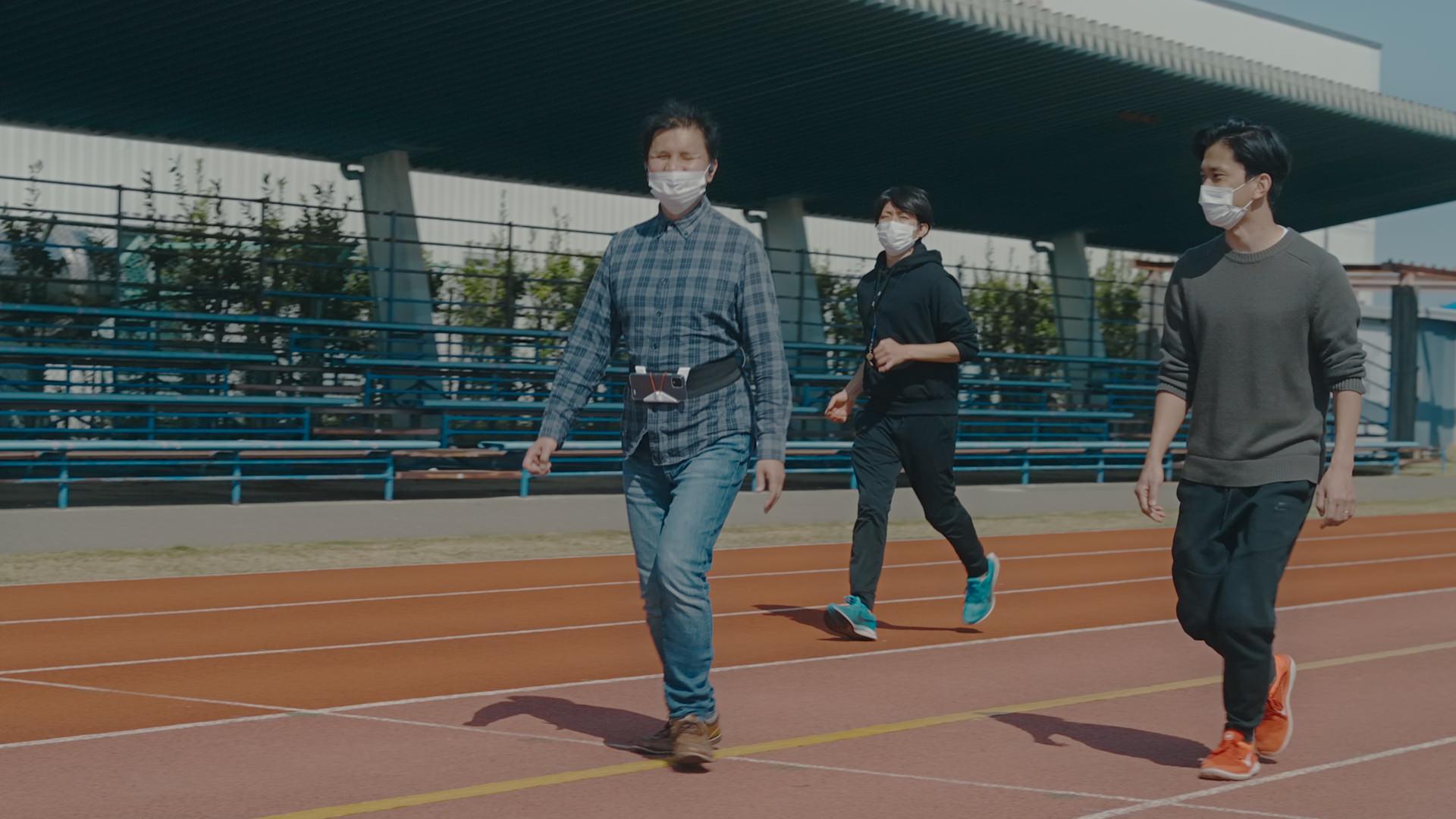 写真:アプリの挙動を確認しながらコース上を歩く男性のテスト走者と、その周りを見守るスタッフ。