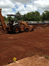 Photo: Workers are grading and compacting the soil for our administration building.  first, though, they needed to take out all of the  roots and other vegetation.