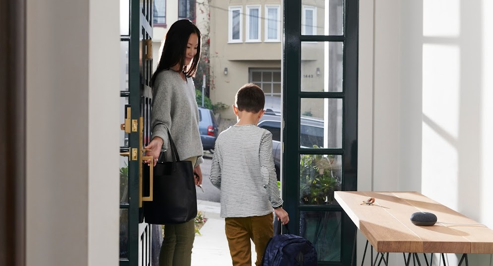 A mom and her son walk out the door with Nest Mini on nearby table.