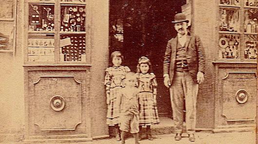 José  Estrade-Berdot en  la puerta de su local de la calle Las Tiendas con sus hijas y el hijo de un tendero vecino. Foto A. Ivorra.