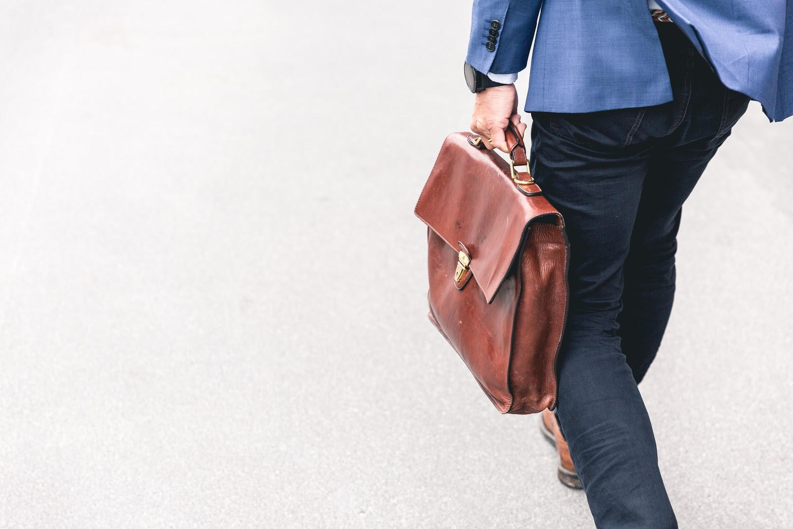Uma pessoa de costas segurando uma mala.