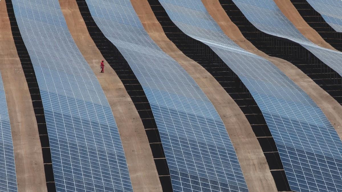 Photo grand angle prise par un drone et représentant un technicien au milieu de rangées de panneaux solaires