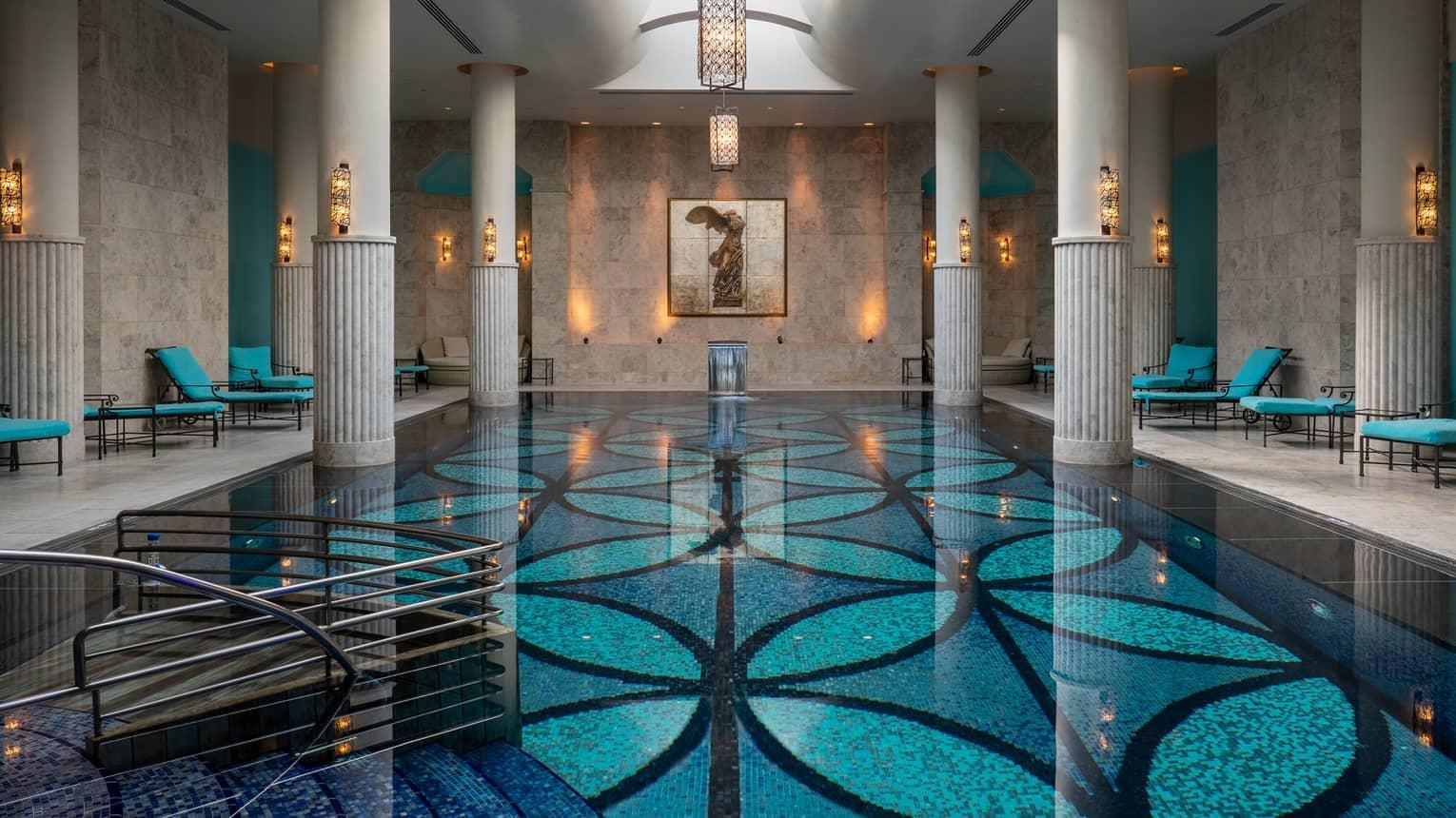 Indoor pool with blue-patterned floor, white up-lit columns and skylight