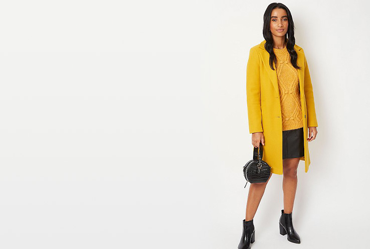 Woman wearing mustard yellow longline coat, matching jumper, black skirt and black boots