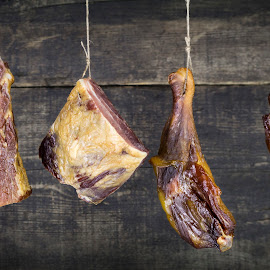 Smoked Meat Hanging on the Rope Against Wooden Background by Aleksandar Ilic - Food & Drink Meats & Cheeses ( lunch, gourmet, spice, pig, leg, red, domestic, ham, fire, wood, smoked, natural, cooked, spicy, brown, delicious, fried, closeup, dish, background, tasty, wing, chicken, crispy, rope, isolated, pork, pork belly, eat, grilled, organic, roast, salty, living, restaurant, smoke, cuisine, eating, dinner, food, drumstick, meal, bacon, fast, healthy, cured, wings, meat, fresh, hanging, chicken thigh )