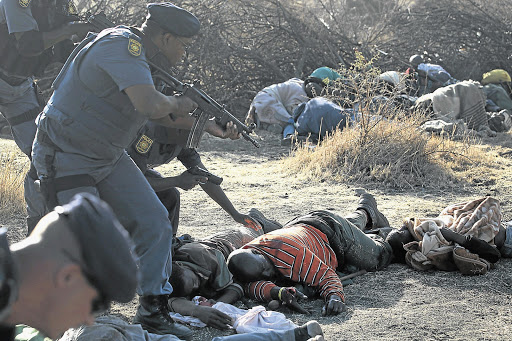 TRAGIC AFTERMATH: Police check on casualties after firing on striking Lonmin mine workers. Locals believe muti prevented many more from being killed